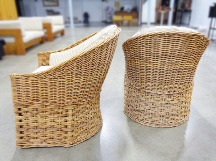 Pair of wicker lounge chairs with cream stripe upholstery.