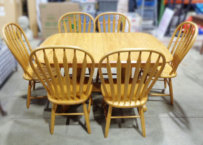 Oak dining table with six Windsor-style dining chairs and three leaves.