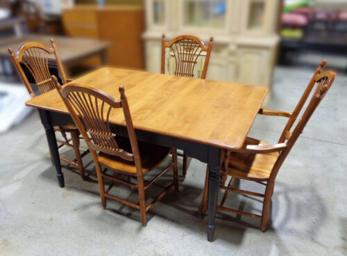 Maple dining table with black painted base and four dining chairs.