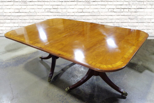 Mahogany dining table with double pedestal base and brass claw feet